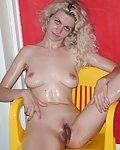 Eingeölte Blondine mit weisser Haut, nackt auf dem Stuhl